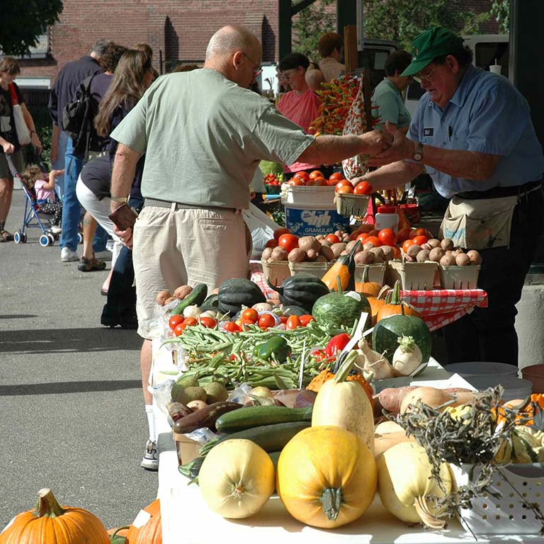 People buying vegetables at the Bloomington Farmers' Market.